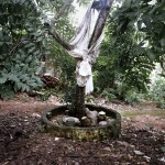 Brazil, Cachoeira, Salvador da Bahia. The sacred tree and pots outside a Candomble Terreiro (Temple) for the specific celebration of the orixa (god) Oxumare, serpent-god of the rain and the rainbow. Oxumare, or Osumare, is also the divinity of the feminine and masculine nature, who has the power to transport the water into the sky and the hearth.