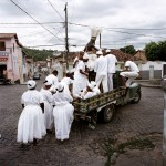 Brazil, Cachoeira, Salvador da Bahia. Worshippers from the branch, or nation (nacoe), of Candomble known as Candomble do Caboclo. The term Caboclo, aside from being a term to describe a person of mixed Brazilian Amerindian and European descent, is also used as an alternate term for certan orixas (gods) of the Candomble religion. The caboclo, that can be seen here on the truck, is also an orixa.