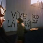 Tunisia, Tunis People walk past graffiti on a wall which reads 'Vive la Liberte'.