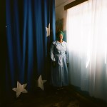 Mozambique, Maputo.  An adherent in a Zion church stands next to a curtain decorated with symbolic stars.