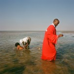 Mozambique, Maputo. During purification rites held on a beach by adherents of a Zion church a woman is ceremonially washed while a pastor walks away to give them privacy.