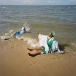 Mozambique, Maputo. Adherents from a Zion church pray together while partly immersed in the surf during a purification ceremony on a beach.