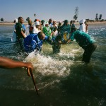 Mozambique, Maputo. A woman in plunged into the sea during a purification ceremony held by adherents of a Zion church on a beach.