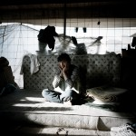 Greece, Patras. 16 year old Hababullah sits on his bed in an abandoned building where he squats.