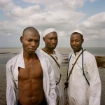 Mozambique, Maputo. Adherents from a Zion church in ceremonial robes during a purification ceremony on a beach.