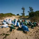 Mozambique, Maputo. Adherents from a Zion church pray together during a purification ceremony on a beach.