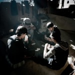 Greece, Patras. Young Afghan refugees play cards in an abandoned building where they squat.