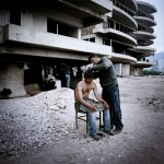 Greece, Patras. Mustafa cuts Arif's hair outside an abandoned building where they squat.