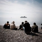 Greece, Patras. A group of refugees sit on a beach as they watch an approaching ship.