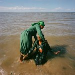 Mozambique, Maputo. An adherant from a Zion church washing another woman during a purification ceremony on a beach.