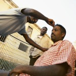 Italy, Palermo, Sicily. Muse (23), an Eritrean, gets a hair cut. He arrived at an immigration reception centre in Italy six months ago, together with 87 other immigrants. He registered for asylum and later moved to Palermo were he as been looking for a job with no success. Thousands of would-be asylum seekers have made the perilous crossing from North Africa to the southern stretch of Sicilian coastline.