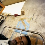 Italy, Palermo, Sicily. Birex (23), an Ethiopian, sleeps underneath a map of Italy at the immigration reception centre. Thousands of would-be asylum seekers have made the perilous crossing from North Africa to the southern stretch of Sicilian coastline.