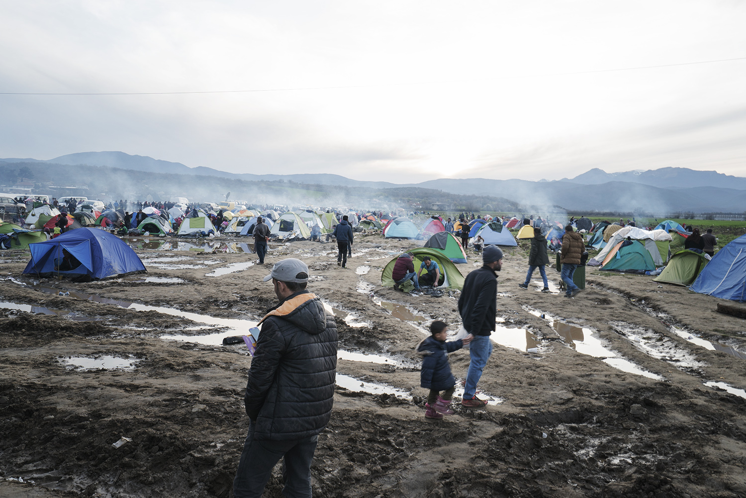 Greece, Idomeni border. Refugees walking down the muddy field, where camping tends have been set up in view of crossing the border. During the first week of March, 50 persons per day were allowed to cross the border with Macedona according to the date of arrival in Greece. As of the second week of March, border closed completely. No one was allowed to cross. As a result, that self-organized and not authorised refugee camp built arond Idomeni train -lane expaned dramatically. Greece, Idomeni border. The border between Greece and Macedonia has become a not recognized refugee camp where approx. 12.000 Syrian and iraqui refugees are awaiting for its reopening in the hope of achieving the German dream. As the meeting between EU and Turkey didn't lead to any changes on the ground, Syrian, Iraqui, Palestinians, Afghans, Pakistani refugees got trapped in that slot of the Greek territory with no way forward. No space for accommodating them is currently available in the existing camps (Diavata, Cherso and Nea Kavala) set up by the Greek Army. As such, prevented from crossing the border and not allowed to enter the camps, refugees will be relying on the international humanitarian assistance and ... on their hope, if it will be still there despite the life-threatening conditions in Idomeni. On March 18th, the EU and Turkey signed a new plan, according to which migrants arriving in Greece will be sent back to Turkey if they do not apply for asylum or their claim is rejected.